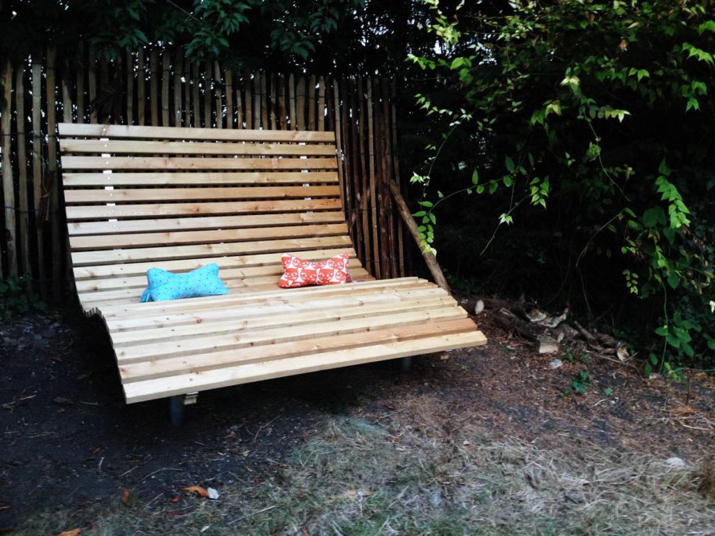 Gartenliege mit zwei Kissen vor Zaun