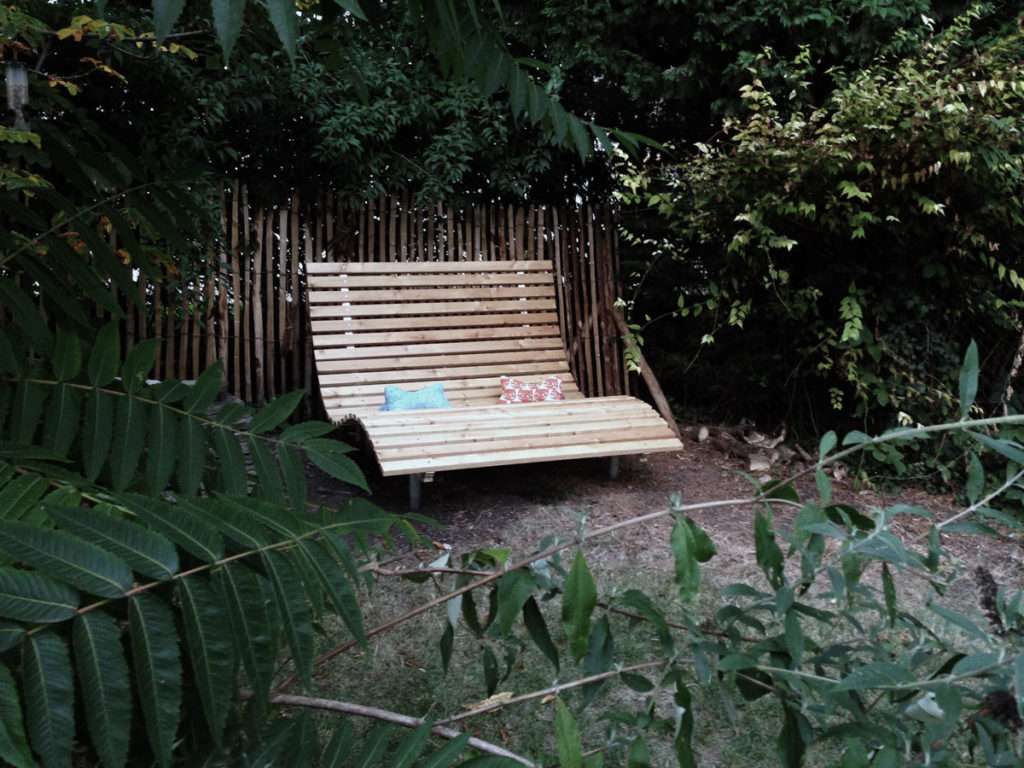 Relaxliege mit zwei Kissen zwischen Hecken