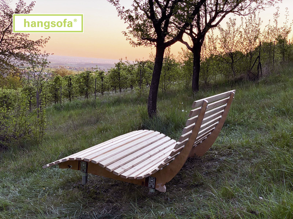 Relaxliege aus Holz im Obsthang bei Sonnenuntergang