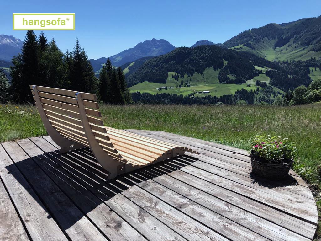 Sonnige Berglandschaft und Relaxliege auf Terrasse