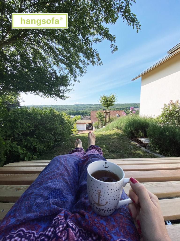 Frau trinkt Kaffee auf einer Gartenliege mit Ausblick ins Tal