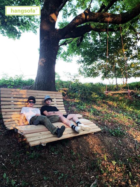 Zwei junge Menschen auf einem Waldsofa unter einem Baum