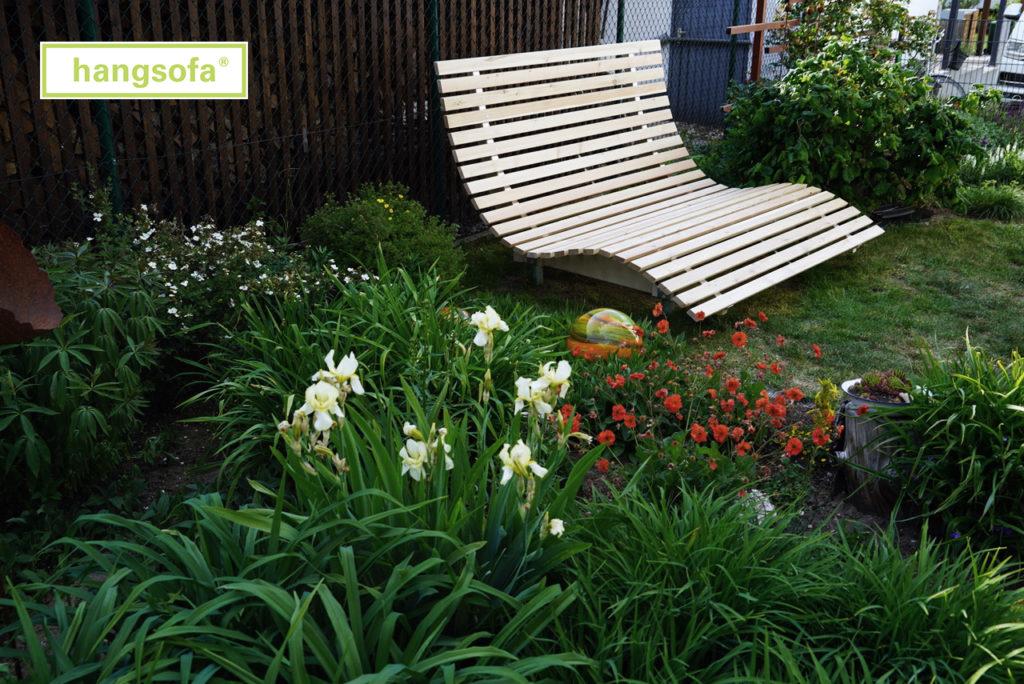 Relaxliege vor einem Blumenbeet