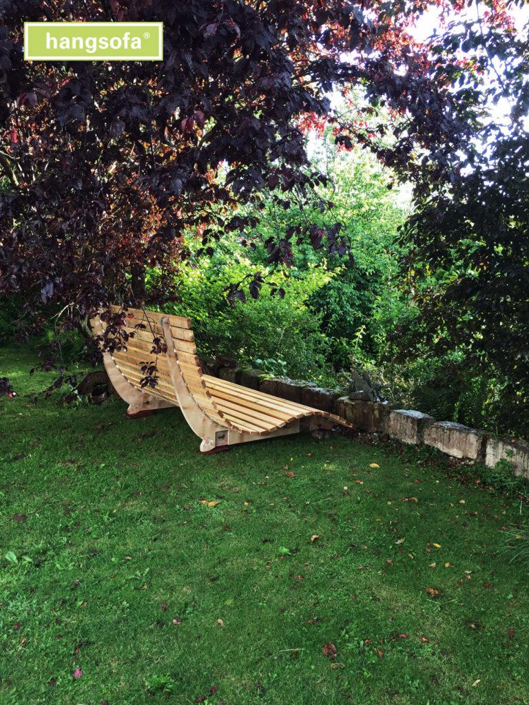 Geschwungene Gartenliege aus Holz unter Bäumen