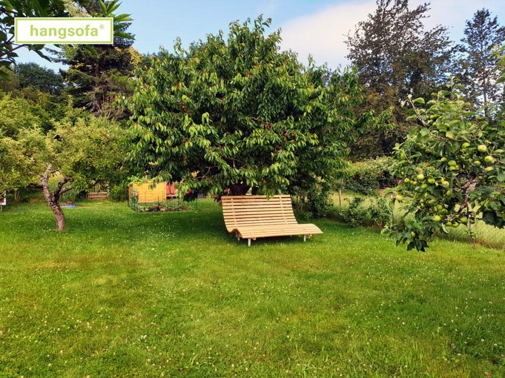 Geschwungene Liegebank unter einem Kirschbaum im Garten