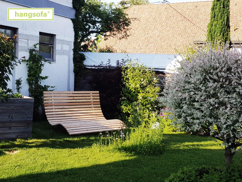 Große breite Relaxliege im blühenden Garten