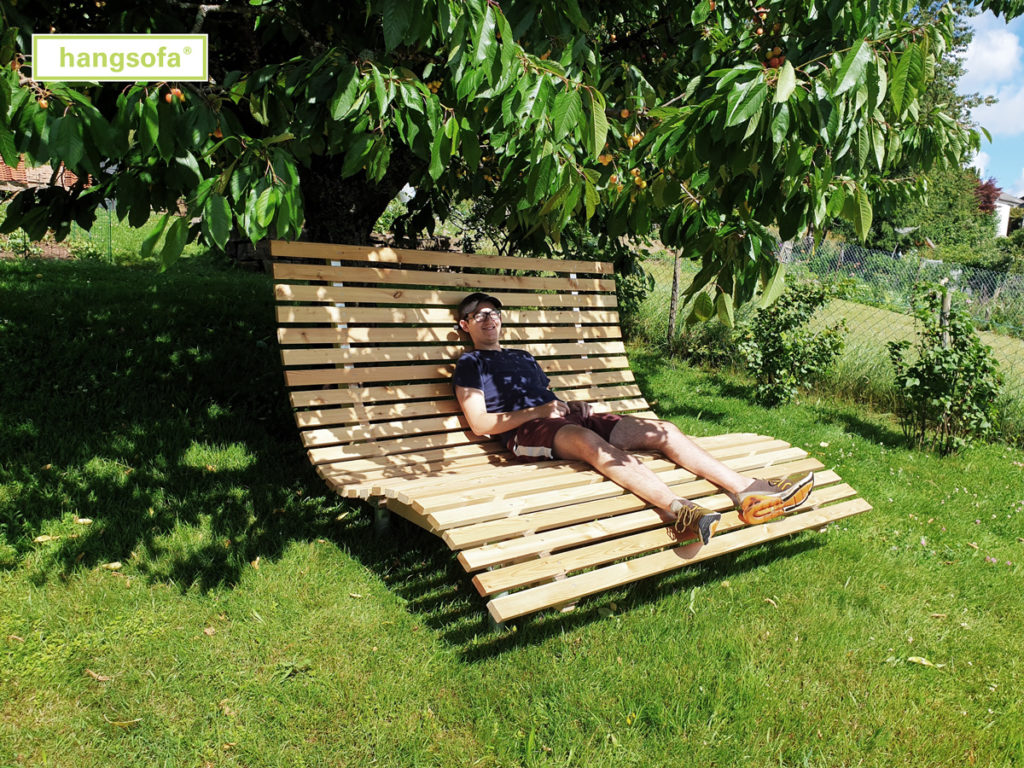 Gartenliege zum Relaxen im Schatten unter einem Baum